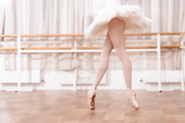 gambe-della-ballerina-che-stanno-sul-pavimento-in-uno-studio-di-ballo_85574-14991